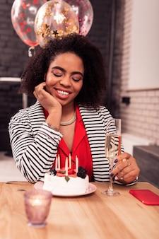 멋진 분위기. 생일 케이크를 보면서 그녀의 턱을 잡고 좋은 사려 깊은 여자