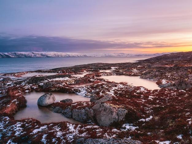 バレンツ海の海岸にある岬のある素晴らしい山の風景。極地の白い雪に覆われた山脈のある素晴らしい日の出の風景。チェベルカ。