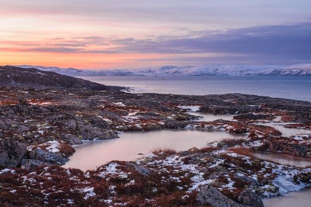 バレンツ海の海岸に岬がある素晴らしい山の風景。極地の白い雪に覆われた山脈のある素晴らしい日の出の風景。チェベルカ。