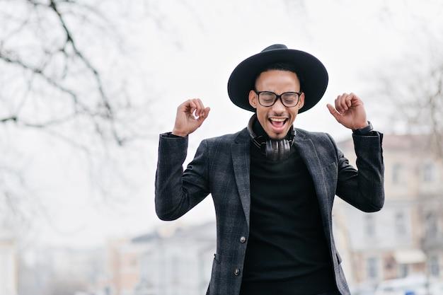 目を閉じて笑っているヘッドフォンの素晴らしいムラート男性モデル。空に立っているのんきなアフリカの若い男の屋外写真