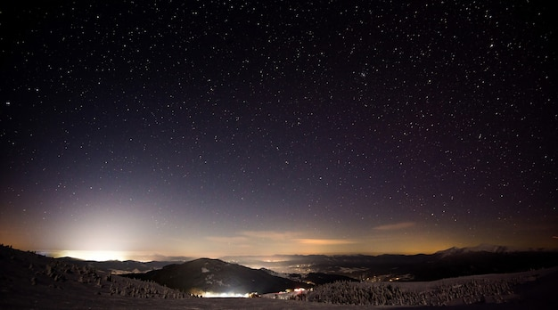 Wonderful night view of the ski resort with hills and slopes against the backdrop of the moon and starry sky. the concept of winter sports and outdoor recreation. copyspace