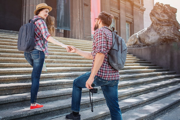 Wonderful picture of two tourists on steps outside on street. he stands lower and hold her hand. she looks back on man and smiles a bit. he has binoculars.