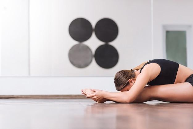 Замечательная пластика. привлекательная молодая трудолюбивая женщина сидит на полу и наклоняется вперед во время разминки