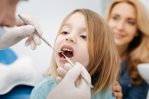 Wonderful pleasant friendly doctor examining his little patients teeth while using special tools providing him better view