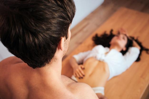 キッチンのテーブルに横になって性交を楽しんでいる素敵なセクシーな若い女性。男は彼女の足に立ってモデルを見る