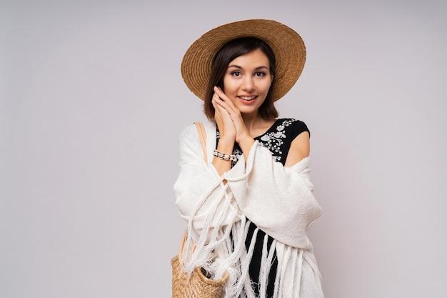 Замечательная коротковолосая женщина в соломенной шляпе и летнем бохо закрывает позирование