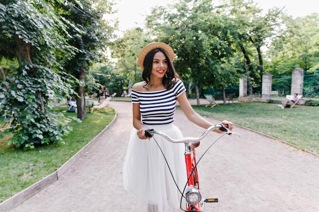 Splendida ragazza timida che cammina intorno al parco verde. romantica signora dai capelli scuri con la bicicletta trascorrere del tempo all'aperto.