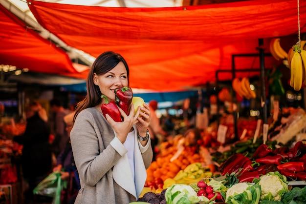 新鮮な野菜の素晴らしい香り。農民市場で美しい女性。