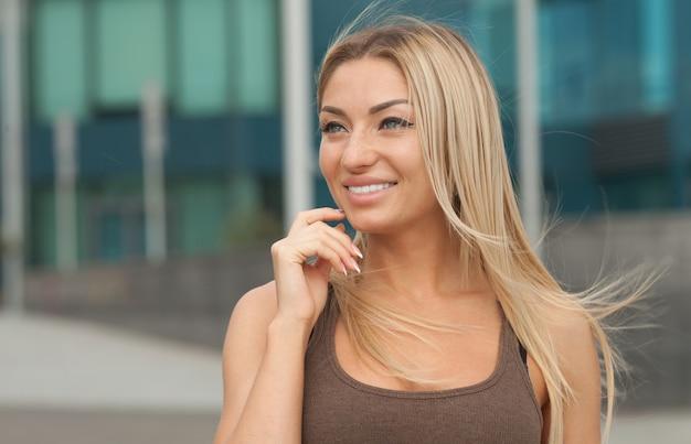 素敵な表情と明るいメイクで素晴らしい笑顔の金髪女性。
