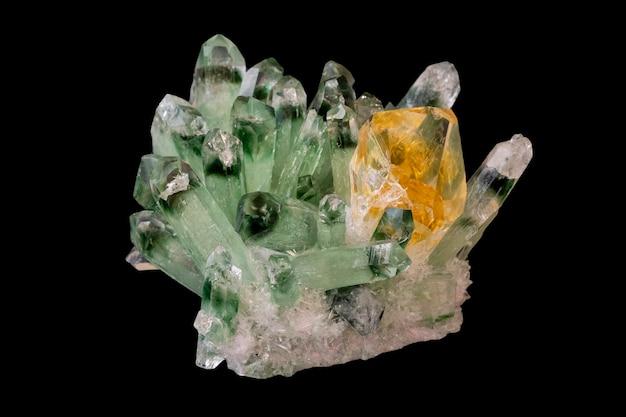 Замечательный сверкающий желтый цитрин среди зеленых кристаллов кварца на черном фоне