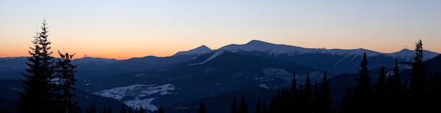 아름다운 별이 빛나는 하늘은 언덕과 나무가있는 산들 사이에있는 스키 리조트의 그림 같은 전망 위에 있습니다.