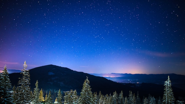 Wonderful starry sky is located above the picturesque views of the ski resort among the mountains of hills and trees. winter vacation concept. place for text