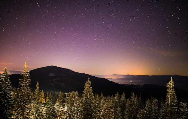 Wonderful starry sky is located above the picturesque views of the ski resort among the mountains of hills and trees