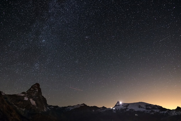 Wonderful starry sky over matterhorn (cervino) mountain peak and monte rosa glaciers background