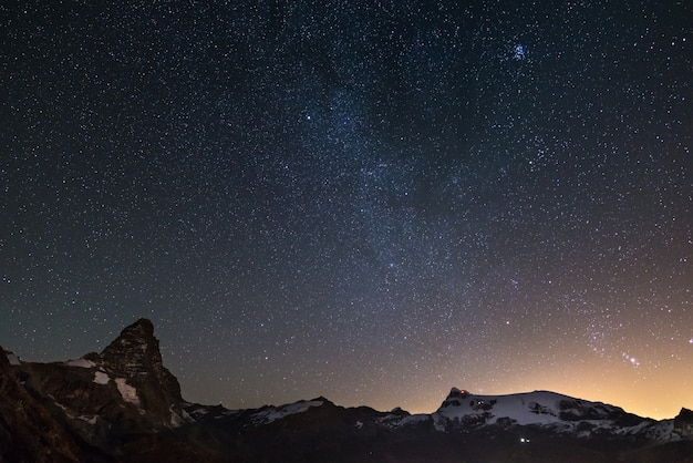 Wonderful starry sky over matterhorn (cervino) mountain peak and monte rosa glaciers.