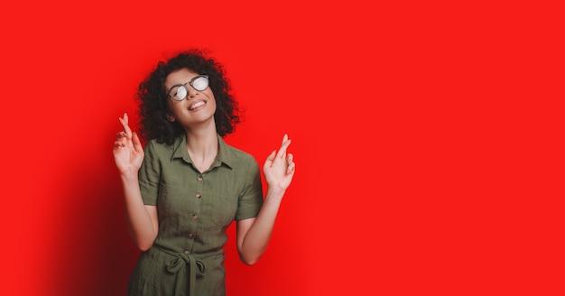 指を組んだ素敵な学生が夢を見ているようで、それが起こることを望んでいるのは美しく笑っています