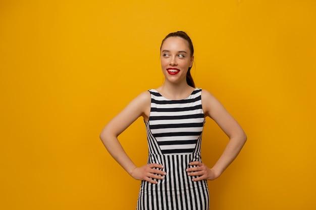 黄色でポーズをとるストリップドレスの素晴らしいスタイリッシュな女の子