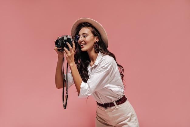 Meravigliosa signora alla moda con un'acconciatura alla moda in orecchini marroni, occhiali trasparenti e abito bianco in posa e tenendo la macchina fotografica