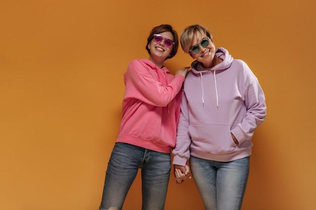 Замечательные стильные две женщины в прохладных солнцезащитных очках и розовых толстовках улыбаются и держатся за руки на оранжевом изолированном фоне.