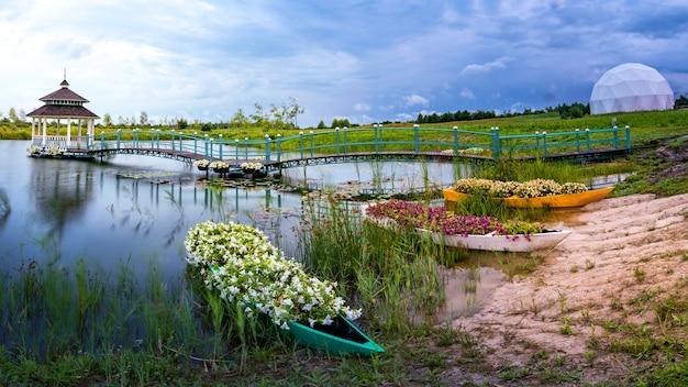 멋진 여름 풍경과 명상의 장소. 나무 전망대, 플랫폼, 호수 옆에 꽃으로 가득 찬 작은 보트 몇 대가 있습니다.