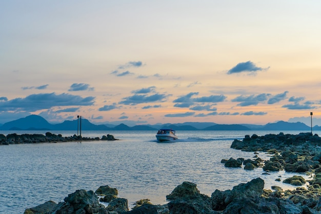 Замечательный закатный пейзаж на берегу моря, цвета закатного неба и силуэт острова в воде, невероятный тропический закат.