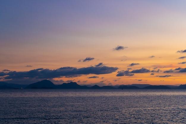 海岸の素晴らしい夕日の風景、夕日の空の色、水に浮かぶ島のシルエット。信じられないほどの熱帯の夕日