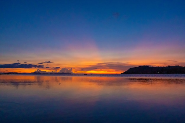 Wonderful sunset landscape on the seashore, colors of the sunset sky and silhouette of island in the water incredible tropical sunset.