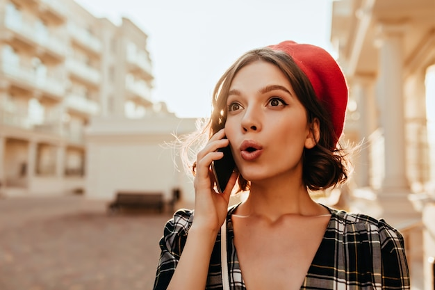 Wonderful surprised girl in red hat talking on phone. magnificent brunette lady with smartphone posing in sunny autumn day.