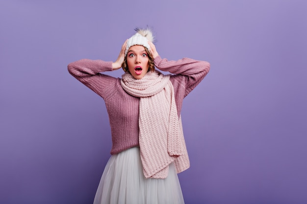 Wonderful surprised woman with knitted scarf touching her head. indoor portrait of shocked caucasian girl in hat and white skirt.