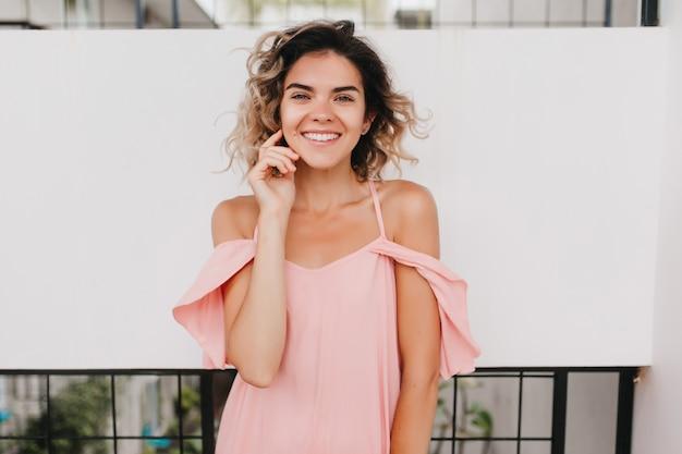 Meravigliosa ragazza abbronzata in abito rosa estivo che tocca il suo viso. ritratto di giovane donna esile che ride con la pelle color bronzo.