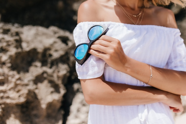 岩の前に立っているエレガントなブレスレットの素晴らしい日焼けした女性。ガラスを保持している白い夏のドレスを着た白人女性の屋外ショット。