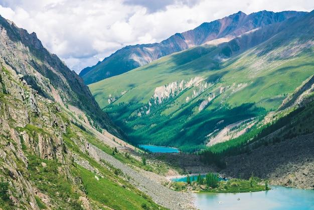 Прекрасные три горных озера в долине горной местности. очистите лазурную поверхность воды. гигантские скалы и горы с богатой растительностью и хвойным лесом. атмосферный зеленый пейзаж величественной природы