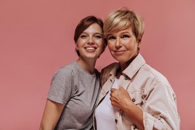 Meravigliose due donne con acconciatura corta moderna in abiti eleganti sorridenti, abbracciando ed esaminando la fotocamera su sfondo rosa.
