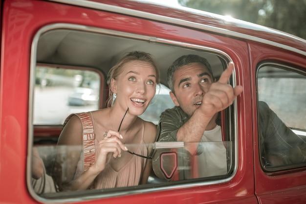 멋진 전망. 도시의 명소를 보고 차 뒷좌석에 앉아 있는 그들을 가리키며 웃고 있는 기혼 부부를 놀라게 했습니다.