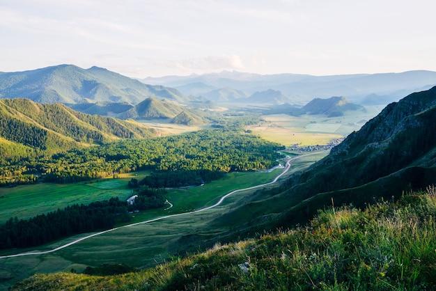 Прекрасный вид с холма с разноцветными травами и цветами на деревню среди великих лесных гор в вечернем свете.