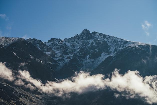 雲の上に雪が降り、頂上が山頂にあるロッキー山脈の素晴らしい景色。尖った山と岩の上の低い雲のある風光明媚な山の風景。鋭い岩の頂点を持つ最小限の高山の風景。