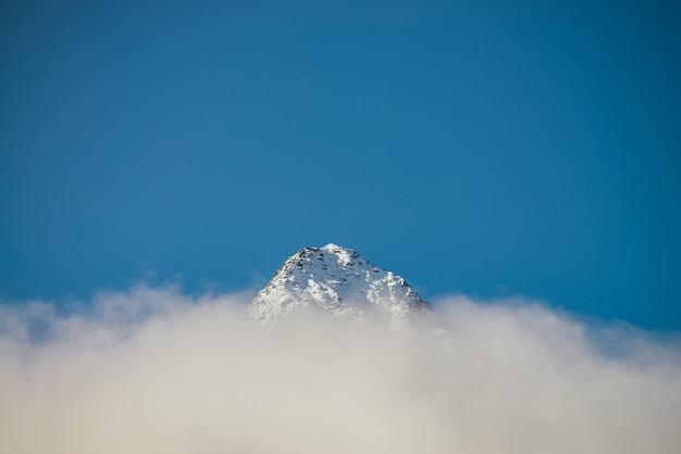 日差しの中で厚い雲の上にある鋭い雪をかぶった山頂の素晴らしい景色。青い空の密集した低い雲の中に白い雪のピークがある明るい山の風景。雪に覆われた頂点のある最小限の風景。