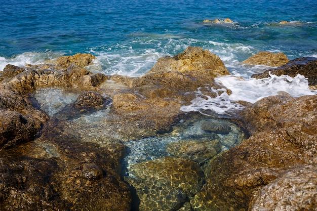 青い地中海の素晴らしい景色。日当たりの良い岩、泡と水しぶきの波。波が岸の岩にぶつかる