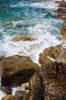 푸른 지중해의 멋진 전망. 맑은 바위, 거품과 물이 튀는 파도. 파도가 해안의 바위에 부딪친다.