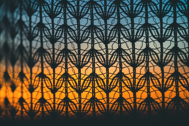 Wonderful vivid dawn from window through patterned curtain. amazing warm sky behind silhouettes of tulle texture.