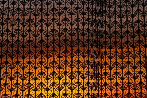 Wonderful vivid dawn from window through patterned curtain.