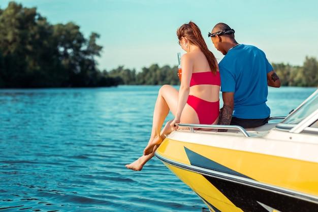 素晴らしい週末。水を見下ろしながらヨットの船首に座っている若いカップル