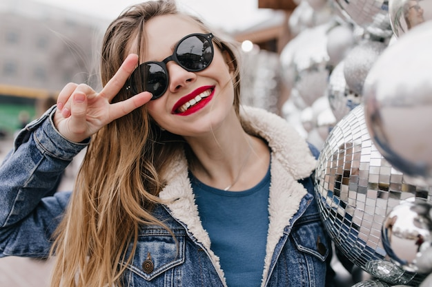 Wonderful white girl in sunglasses posing with peace sign in cold spring day. outdoor shot of laughing female model in denim jacket having fun in morning.