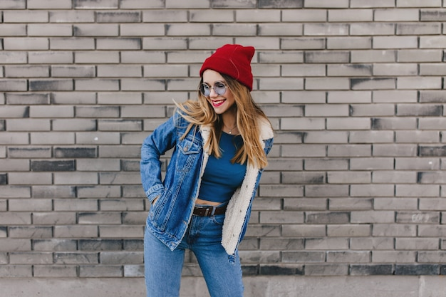 Meravigliosa signora bianca con cappello rosso che balla felice per strada. foto all'aperto di bella ragazza bionda in vestiti di jeans divertendosi sul muro di mattoni.