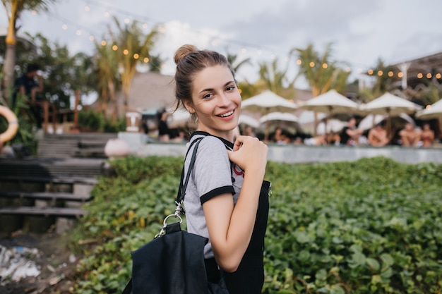Wonderful white woman chilling at summer resort in evening. laughing brunette girl with black bag looking over shoulder on nature.