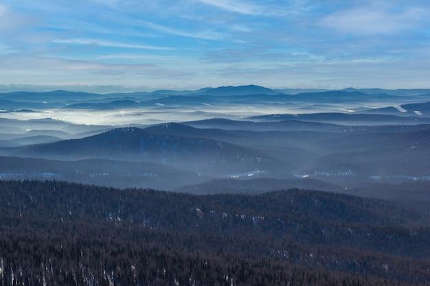 화창한 날에 멋진 겨울 산 풍경입니다. 안개 속에서 거리에있는 산.