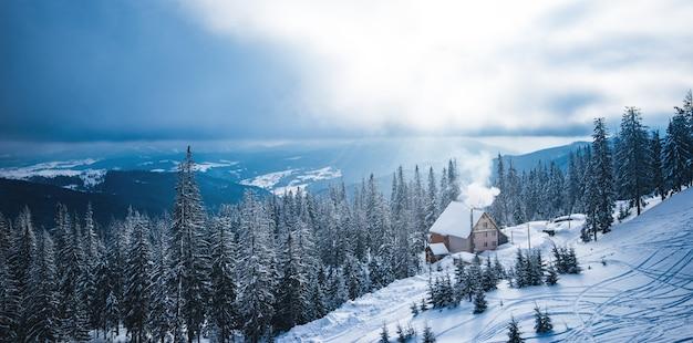 Замечательный зимний отдых пейзажем лесных горок и гостевого дома с дымом из трубы.