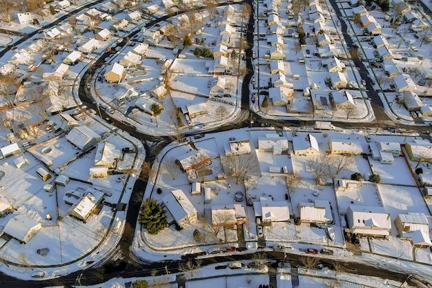素晴らしい冬の風景の屋根には、雪が降った後の冬の日に雪が降る住宅の小さな町と空中写真で覆われた雪の木があります