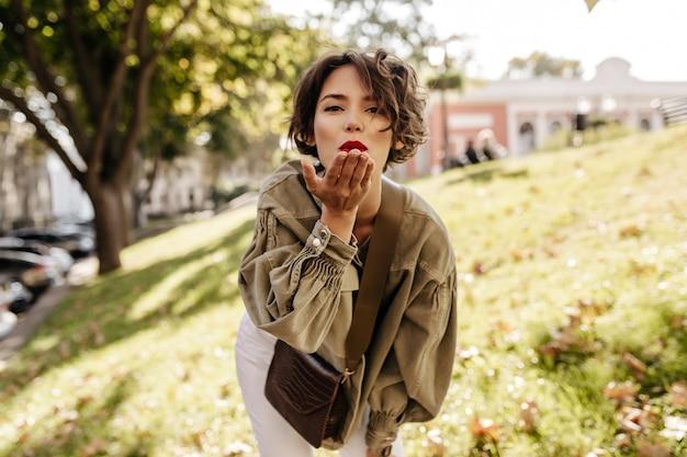 Meravigliosa donna in giacca di jeans e pantaloni bianchi che soffia bacio fuori. donna castana con labbra rosse con borsetta in posa all'aperto.