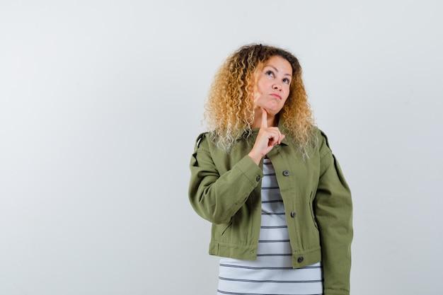 Meravigliosa donna in giacca verde, camicia tenendo il dito sotto il mento, alzando lo sguardo e guardando pensieroso, vista frontale.
